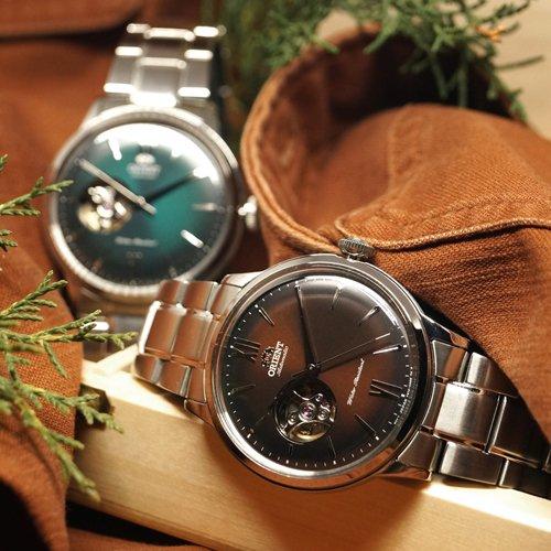 Męskie zegarki Orient z tarczami open heart w dwóch kolorach czerwonym oraz zielonym na srebrnej bransolecie.