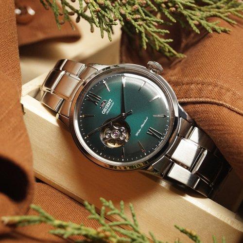 Klasyczny zegarek Orient z zielona tarczą open heart na srebrnej bransolecie.