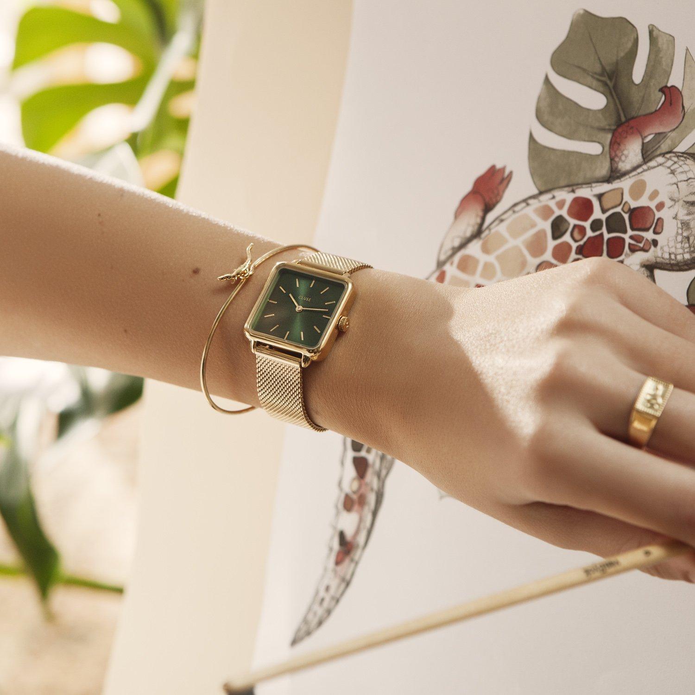 Mosiężna koperta w złotym kolorze idealnie komponuję się z ciemną tarczą zegarka Cluse CL60014 Gol/Forest Green.