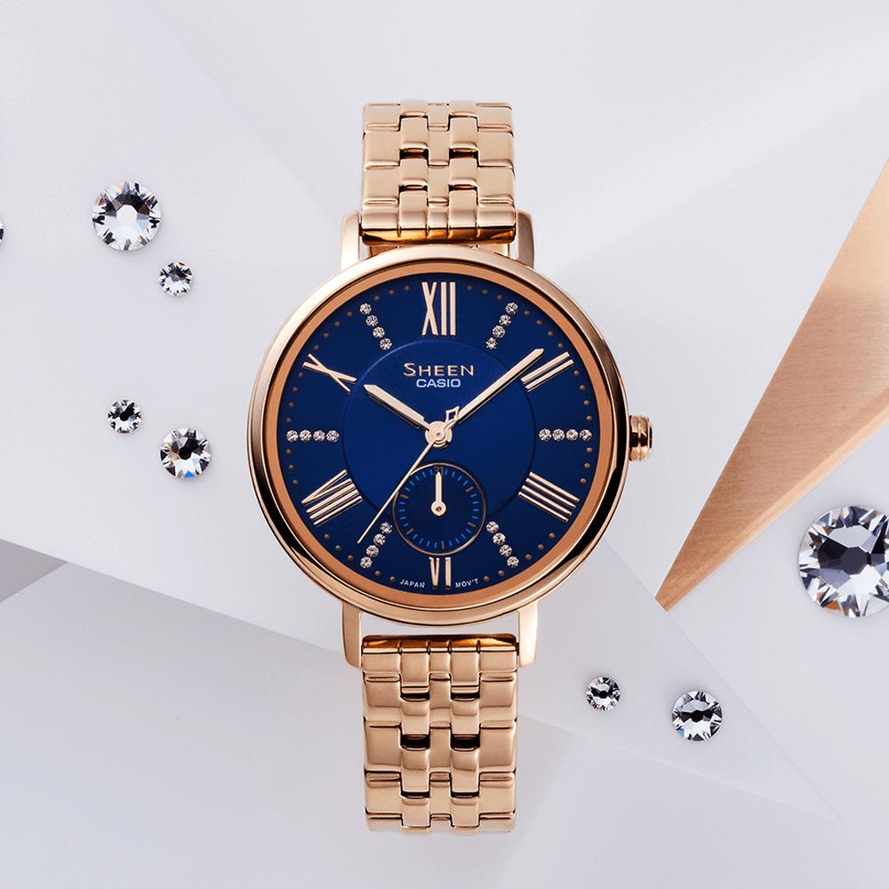 Kobiecy zegarek Casio Sheen na bransolecie w kolorze różowego złota na ciemnoniebieskiej tarczy na której kilka indeksów ozdobione jest kryształkami Swarovskiego.
